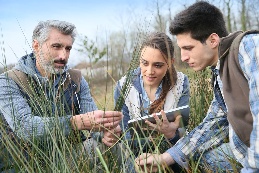 Teacher with students in agronomy looking at vegetation.jpeg