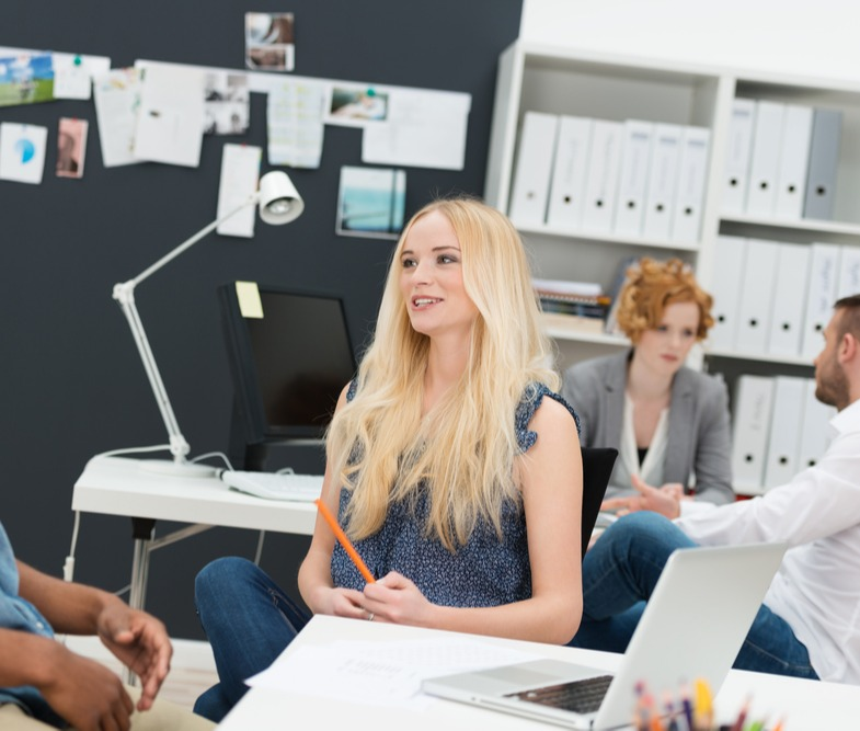 Two young businesspeople in a busy office sitting chatting with a beautiful young blond woman and young African American male in the foreground and colleagues working behind-2